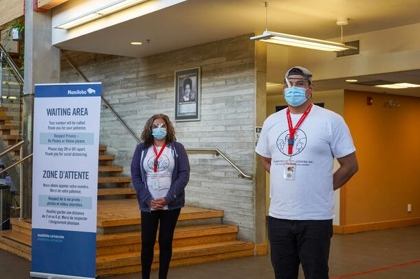 Two individuals wearing masks and protective eye wear standing in the waiting area of the Urban Indigenous Vaccination Centre at Win Gardner Place.