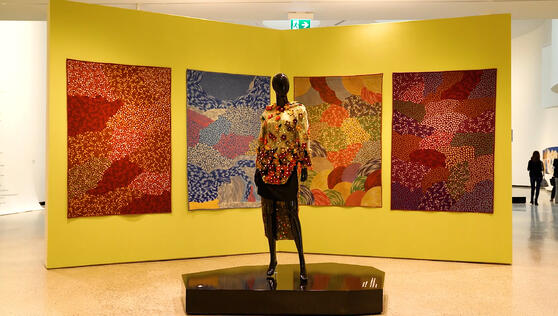 A large wall with four blanket art pieces handing on it. A mannequin stands on a platform in front wearing clothes by an Inuit designer.