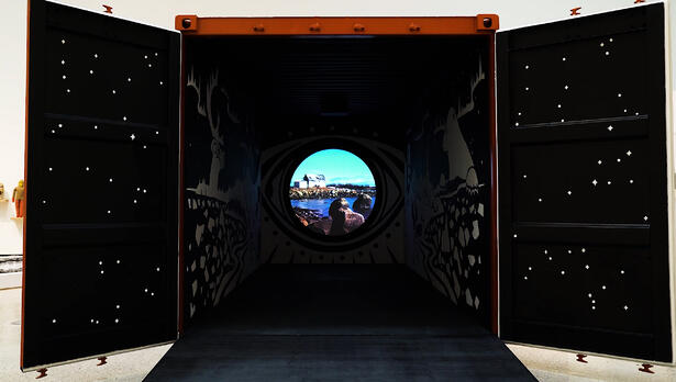 A large shipping container. It's open and inside features both traditional and emerging media.