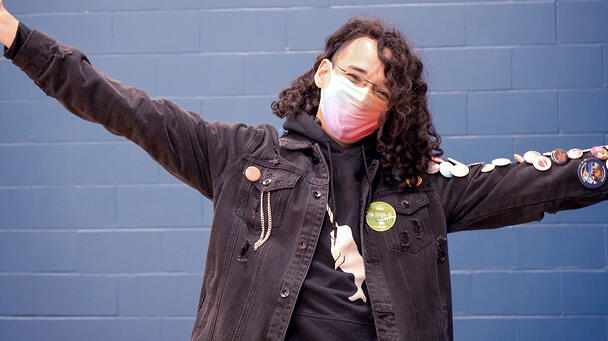 An individual wearing a mask with a vaccination sticker, holding their arms out in celebration.