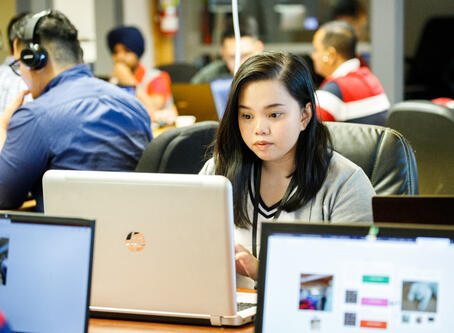 A Red River College student working on a laptop.