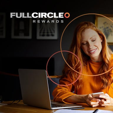 A woman sitting at her desk in a home office with a laptop in front of her. She's looking down at the desk and smiling. Text reads: Full Circle Rewards -FullCircleRewards.ca.