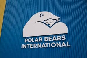 "Polar Bears International logo on the side of their building; a larger polar bear hugging a small baby polar bear with the words ""Polar Bears International"" written underneath."