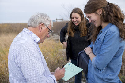 Lake Winnipeg Foundation Programs Director Chelsea Lobson (centre) joins volunteers Peter Williams and Danica Racicot as they collect water samples at Cooks Creek as part of the Lake Winnipeg Community-Based Monitoring Network.