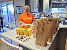 Payworks Technical Writer Rachel Wolman in her kitchen wearing a hair net. There are several kraft paper bags and lunch items on the counter in front of her.