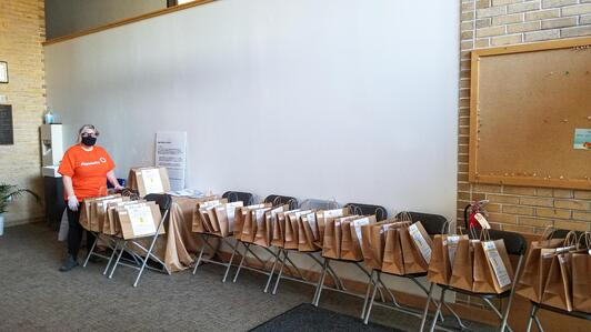 Payworks Technical Writer Rachel Wolman standing at the far end of a long line of chairs with gift bags on them.