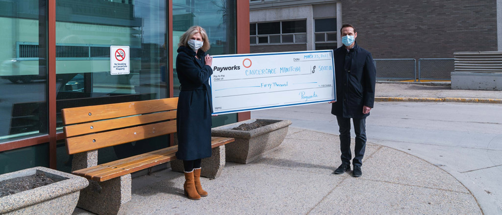 Patti Smith, President and CEO of CancerCare Manitoba Foundation with Payworks President & CEO JP Perron outside of the CancerCare Manitoba building in downtown Winnipeg. They're holding a large cheque for $50,000 and are both wearing masks.