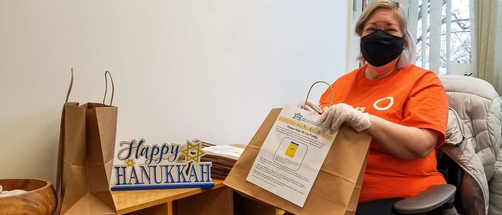 Payworks Technical Writer Rachel Wolman standing in her kitchen wearing a hair net. There are several kraft paper lunch bags on the counter with lunch items such as sandwiches and juice boxes.