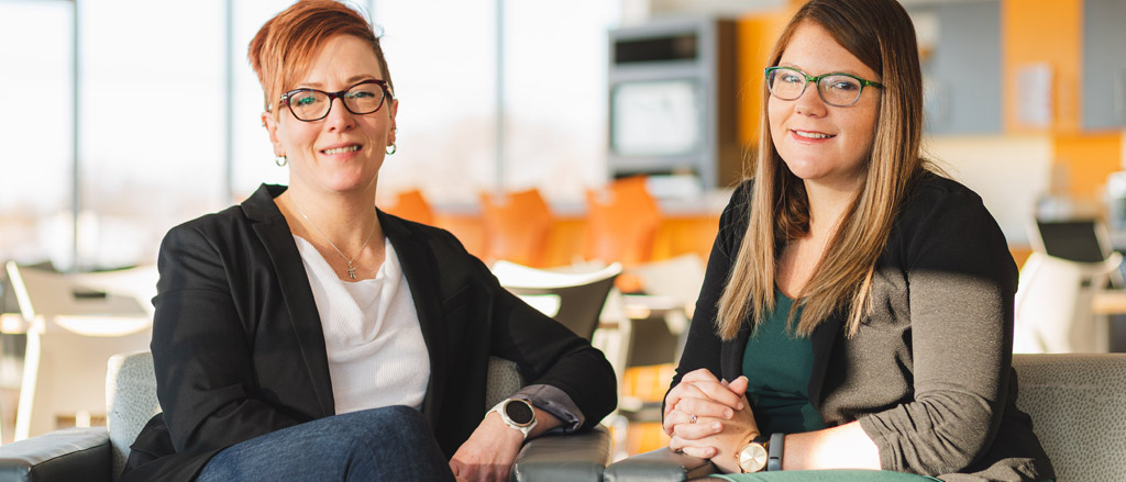 Une photo datant de 2019 montrant Nicole Stewart, vice-présidente des ressources humaines de Payworks, et Candace Synchyshyn, directrice des ressources humaines, assises sur un sofa dans les locaux de Payworks.