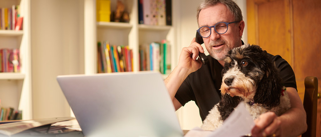 An older man with glasses sitting at a home office desk with a laptop open in front of him and a bookshelf behind him. He's on the phone and is looking down at some papers on his desk. There's also a black and white dog sitting on his lap looking off into the distance.