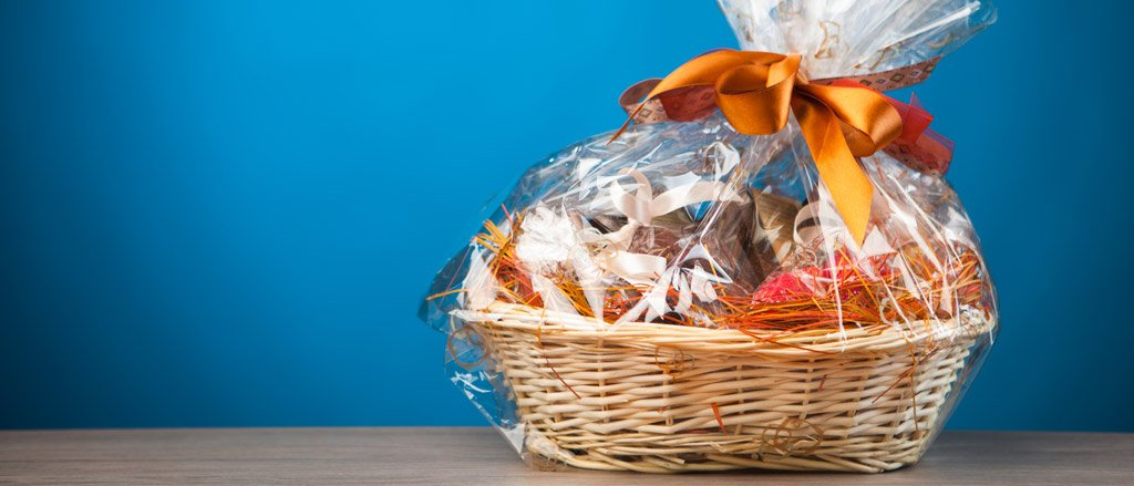 A wicker gift basket with lots of goodies inside it, wrapped in cellophane wrapping and an orange ribbon tied into a bow. The gift basket is on a wooden table and there is a sky blue background behind it.