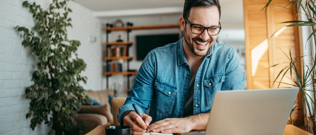A man sitting at a desk in his home office with an indoor plant and a living room TV wall unit behind him. He's looking forward at his open laptop while laughing. He also has a notebook in front of him and is taking notes. He's wearing a long sleeve denim shirt and black glasses.