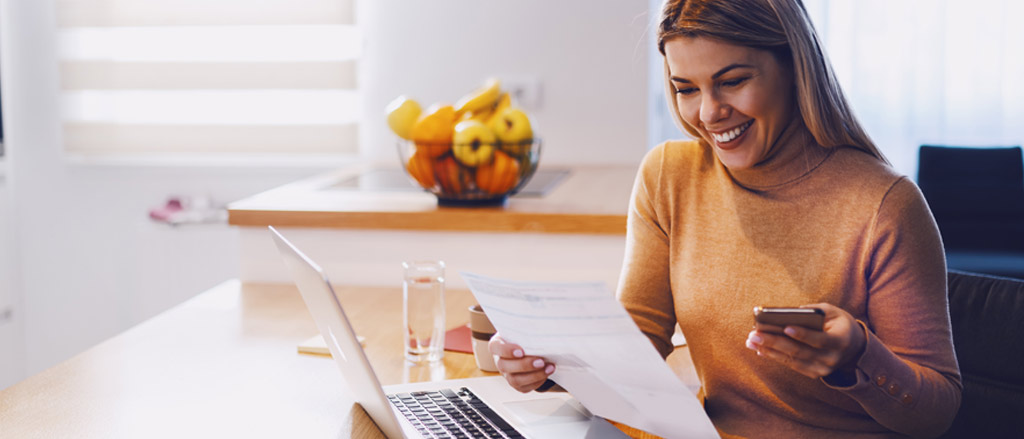A woman sitting at her kitchen table, using it as an at home workspace. There is a fruit bowl behind her on the counter and her laptop is open in front of her. She's holding her cell phone and looking down at a piece of paper. She's smiling at what she's looking at.