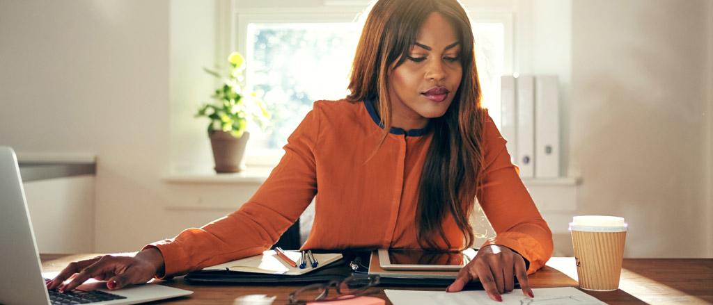Une femme assise à son bureau : un ordinateur portable est ouvert à sa gauche et sa main est sur le clavier. Elle regarde une feuille sur le bureau, sur lequel elle désigne une référence. Sur le bureau devant elle, on voit des notes autocollantes orange, une paire de lunettes de lecture, une tasse de café à emporter, un bloc-notes et quelques crayons. On voit derrière elle une grande fenêtre, à la droite de laquelle se trouvent des reliures. Une plante est disposée à gauche.