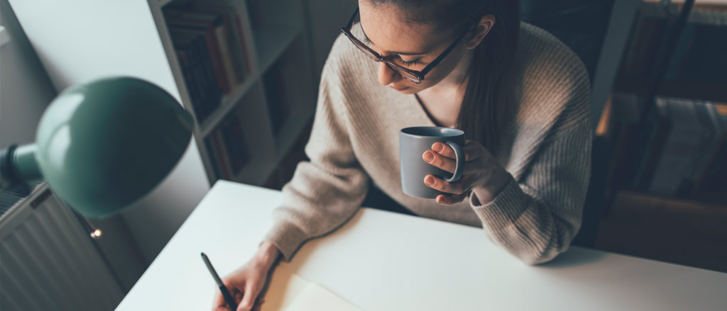 A woman sitting in a home office, with a grey coffee mug in one hand and writing on a notebook with the other. She is looking down at the piece of paper, her long brown hair is pulled back in a ponytail and she's wearing dark rimmed glasses and a beige long sleeve sweater.