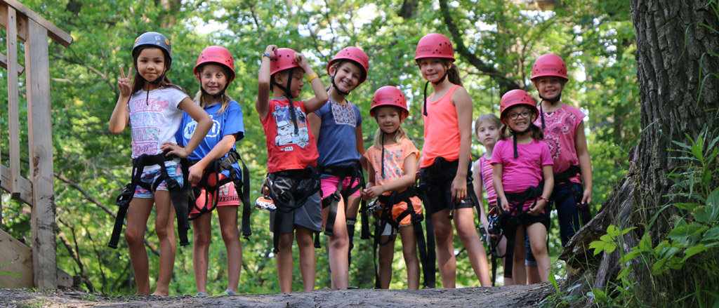 """A kid on a zip line. Text reads, """"Celebrating diversity, inclusion and belonging with Camp Manitou""""."""