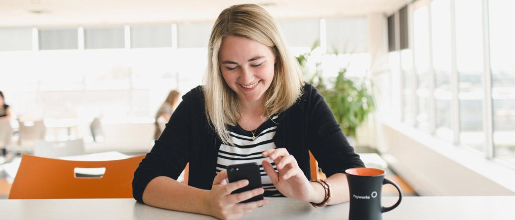Une femme dans sa mi-vingtaine assise à un comptoir regarde son téléphone en souriant.