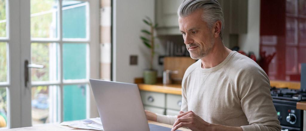 Homme travaillant à la maison sur son ordinateur portable