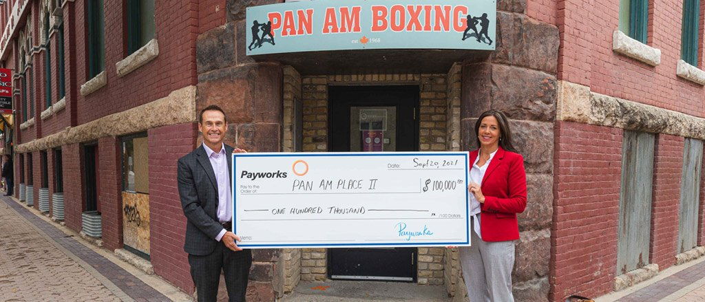 """Two indivduals holding a large cheque for $100,000 under a sign that says Pan Am Boxing. Text reads, """"Supporting holistic health at Pan Am Place 2""""."""
