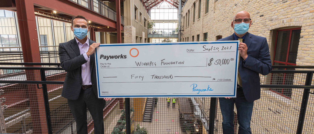 """Two individuals holding a large cheque for $50,000. Text reads, """"Introducing Payworks Education Award""""."""