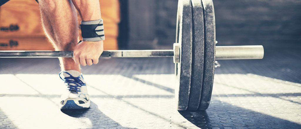 A close up photograph of on end of a barbell on a gym floor with three weights on the end. You can see an arm and a leg of a man getting ready to pick it up wearing runners and wrist supports.