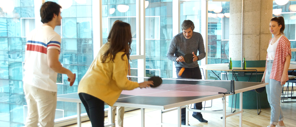 """An employee games room with staff playing foosball and skateboarding. Text reads, """"What ACTUALLY builds employee engagement""""."""